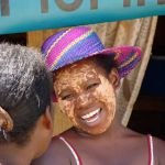 Meisje met klei op gezicht, wat gebruikt wordt als zonnebrand